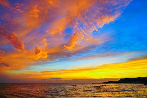 海の上の日没の黄金の雲
