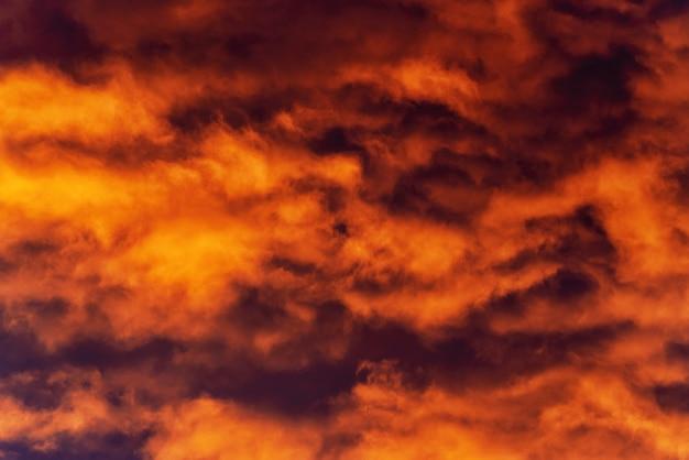 天気を変えるために空の劇的な濃い紫と紫の雷雲を横切って浮かぶ日没で消える光線によって照らされた金色の雲。自然気象学の背景。モーションブラー、ソフトフォーカス