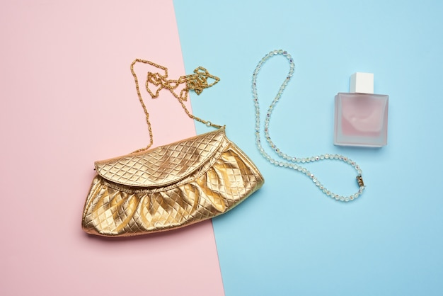 Golden clutch bag with various cosmetics and jewelry on a blue background