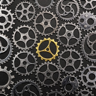 Golden cogwheel surrounded by metal cogwheels.