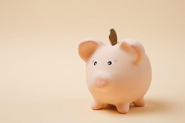 파스텔 베이지색 배경에 격리된 분홍색 돼지 저금통에 황금 동전이 떨어졌습니다. 돈 축적, 투자, 은행 또는 비즈니스 서비스, 부의 개념. 공간 광고를 조롱하십시오.