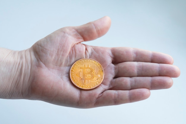 Золотая монета биткойнов под рукой. цифровые виртуальные деньги