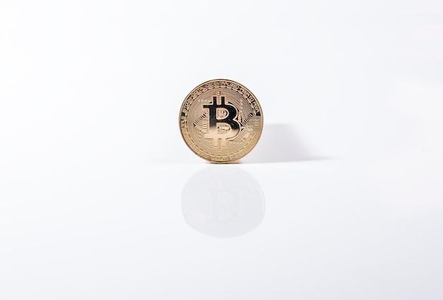 Золотая монета биткойна на белом фоне с отражением