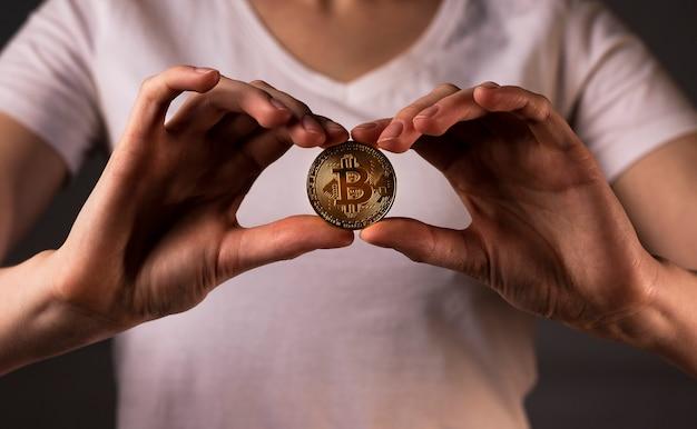 Btcまたはビットコインのゴールデンコインは女性の手で持っていました。