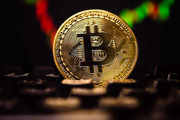 A golden coin with bitcoin symbol on computer keyboard with stock graph background.