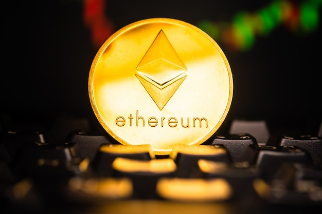 A golden coin with ethereum symbol on computer keyboard with stock graph background.
