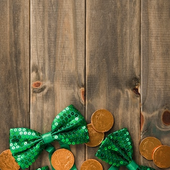 Golden coins and bow ties on wooden board