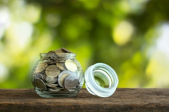 Golden coins in a glass jar on wood table with blurred nature background