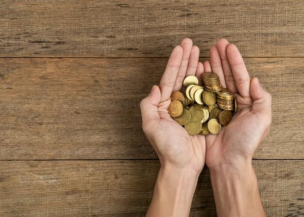Золотые монеты в руке на поверхности деревянной доски.