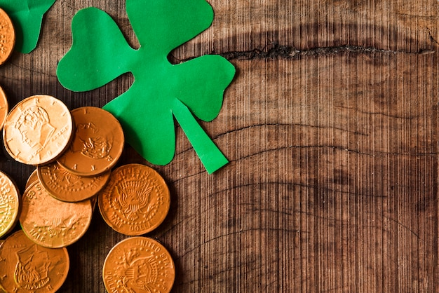 Golden coins and paper shamrocks on wooden table
