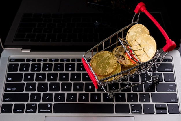 Golden coins with bitcoin symbol in a little shopping cart on a computer keyboard.
