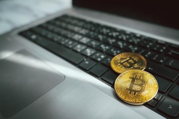 ノートパソコンのノートパソコンのキーボードにビットコインのシンボルと黄金のコイン