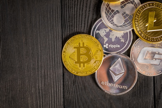 Golden coins with bitcoin, on wood.