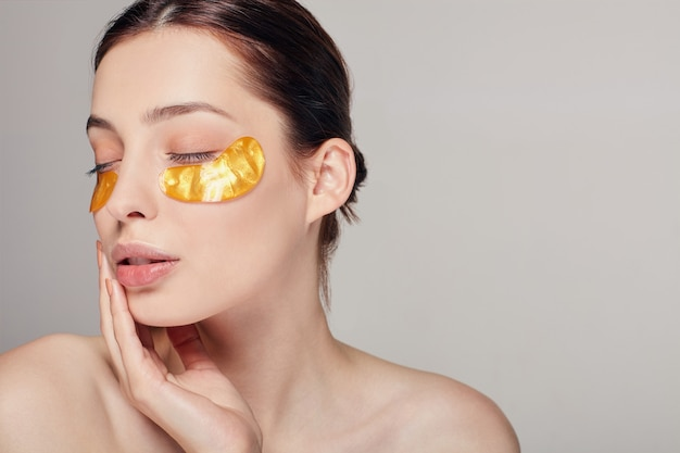 Golden collagen patches under her the eyes. remove wrinkles and dark circles. a woman takes care of delicate skin around her eyes. cosmetic procedures. facial skin.