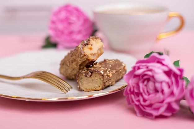 Эклеры золотистого цвета на тарелке с вилкой и чашкой чая