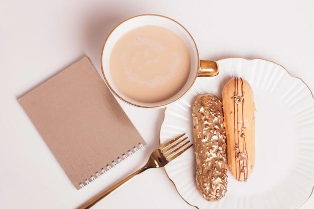 Золотые эклеры на тарелке с ножом и вилкой с чашкой кофе на светлом фоне