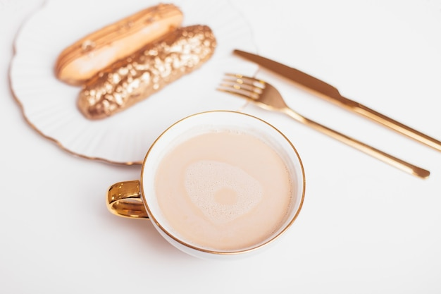 Golden colored eclairs on plate knife and fork cup of coffee