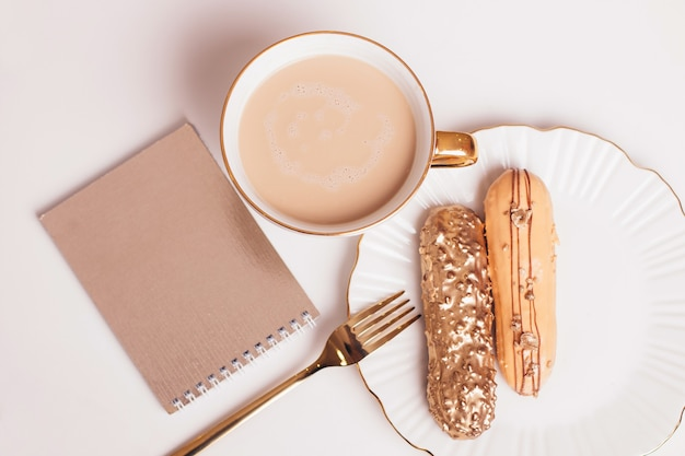 Golden colored eclairs on plate with knife and fork with cup of coffee on light background