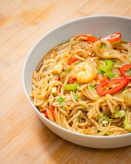 Golden coloured spicy sea food noodles with shrimp, broccoli, chilli pepper in a plate on wooden table