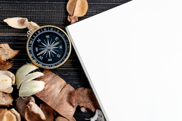 Golden compass put on dried leaves and blank notebook on wooden retro black table.