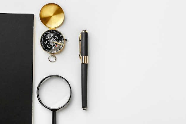 Golden compass with black notepad and pen close up on a table