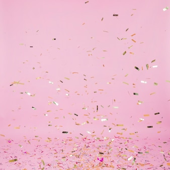 Golden confetti falling on pink background
