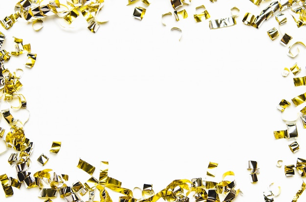 Golden confetti and foil tape on white background.