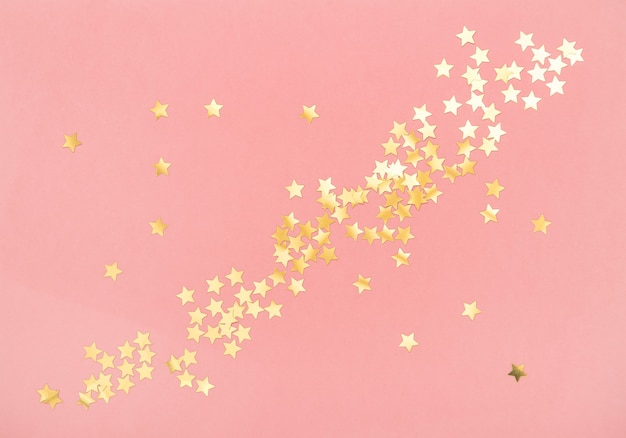 Золотое конфетти на розовом цветном фоне. праздники плоская планировка