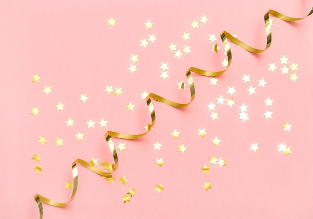 Golden confetti and serpentine on pink color flat lay background