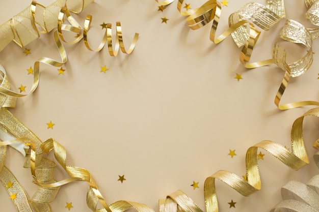 Golden confetti, tapes on beige background. christmas composition. festive holiday backdrop.