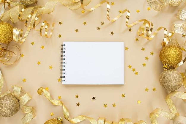 황금 색종이, 테이프, 베이지 색 배경에 빈 노트북. 크리스마스 composition.flat lay, top view