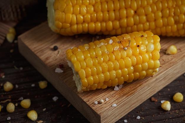 素朴な木製のテーブルに油、ハーブ、塩と黄金のトウモロコシの穂軸