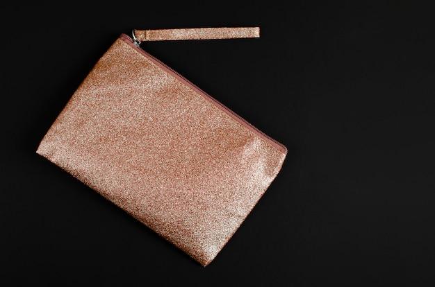 Golden cosmetic bag on black .
