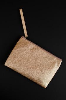 Golden cosmetic bag on black