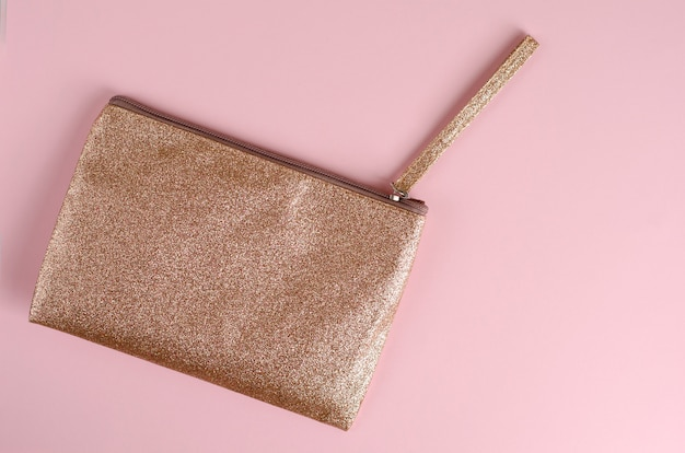 Golden cosmetic bag on pastel pink