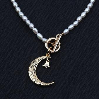 黒のテクスチャ背景に真珠のネックレスと黄金の三日月形のペンダント
