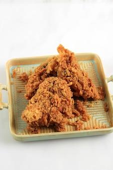 골든 크리스피 프라이드 치킨 가슴살과 치킨 윙, 칠리 소스와 함께 소박한 사각형 접시에 제공, 텍스트 복사 공간이 있는 흰색 배경에 고립