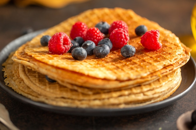 Golden crispy round waffles served on plate with berries. closeup.