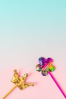 黄金の王冠とピンクの花はグラデーションのピンクとブルーの背景に丸いスパンコールで作られました。コピースペースとファッションパーティーアクセサリー。お祝いフラットレイアウト。最小限のスタイル。