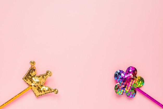 黄金の王冠とピンクの花はピンクの背景に丸いスパンコールで作られました。コピースペースとファッションパーティーアクセサリー。お祝いフラットレイアウト。最小限のスタイル。