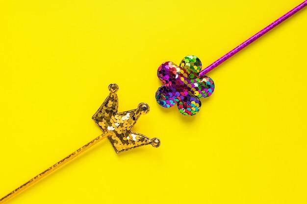 黄金の王冠とピンクの花は黄色の背景に丸いスパンコールで作られました。コピースペースとファッションパーティーアクセサリー。お祝いフラットレイアウト。最小限のスタイル。