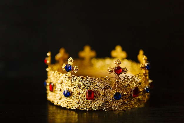 Golden crown encrusted with blue and red gemstones on a black background