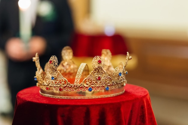 교회 전통 결혼식에서 붉은 식탁보에 보석이 있는 황금 왕관