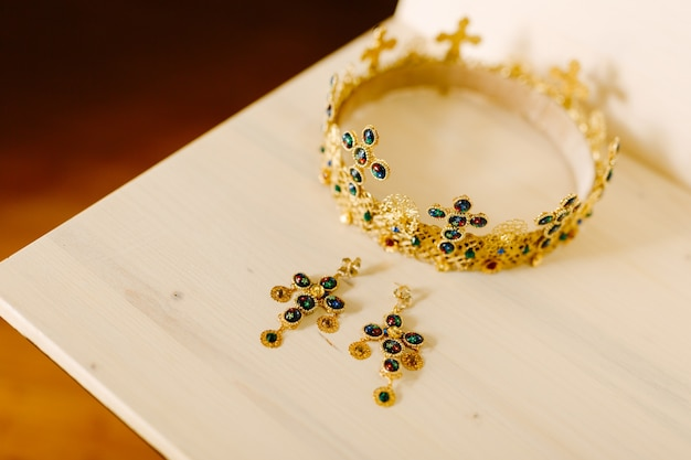 Golden crown with wedding crosses and gold earrings encrusted with precious stones