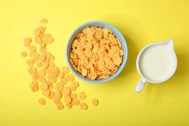 Golden and crunchy cornflakes on a colored background closeup