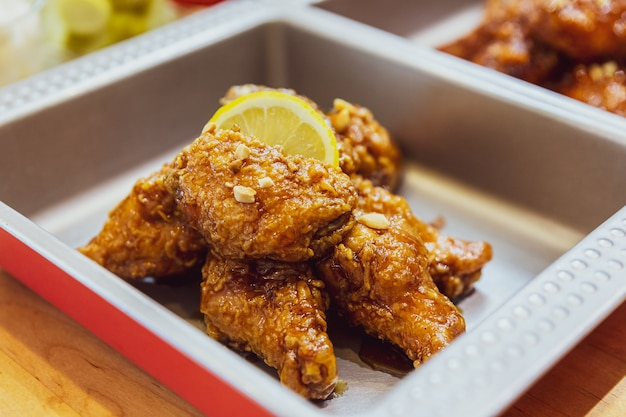 Golden crunchy korean fried chicken (basic huraideu-chikin) mx with garlic sauce and sliced lemon.