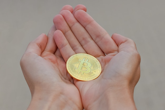 A golden cryptocurrency bitcoin coin on the elongated woman's hands on a grey surface. a women hands are holding a golden big coin of bitcoin.