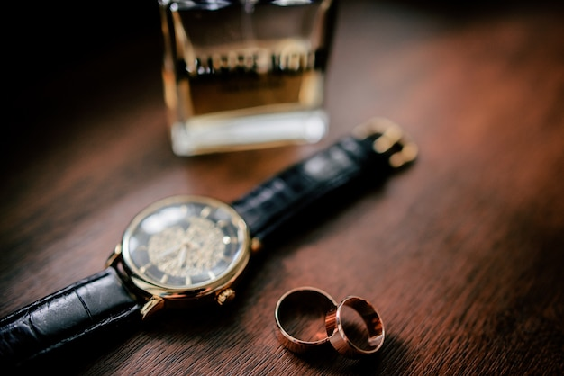 Golden cufflings, wedding rings and watch lie on wooden table