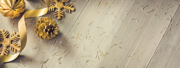 Golden curly ribbon and shimmer christmas decorating items on wood banner background