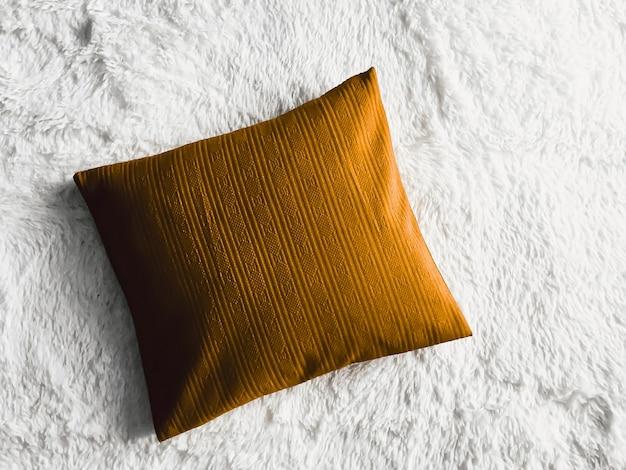 金色のクッションが白いふわふわの格子縞の毛布に枕を投げ、フラットレイの背景の寝室の上面図として...